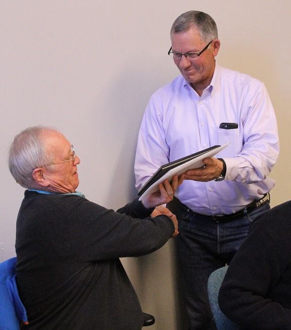 Mayor Dave Sakrison is presented service plaque by Commissioner Bruce Adams